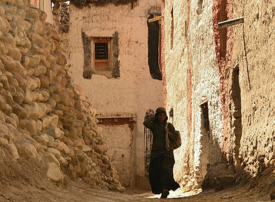 Woman walking in alleyway in Lo-Manthang, capita of UpperMutang, Nepal