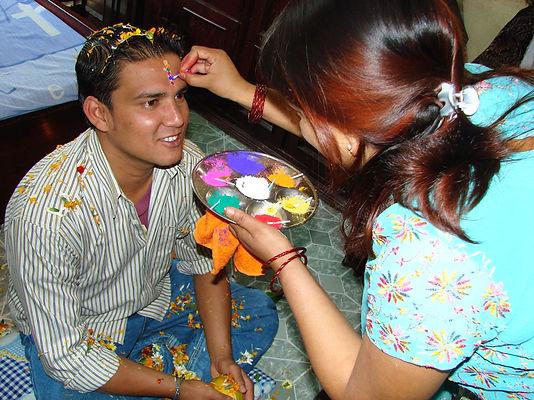 Sister placing tika on brother's head, Bai Tika, Nepal