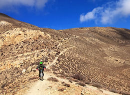 Mountain bikerider descending on trail in Upper Mustang, Nepal