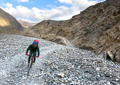 Mountain bike riding up stone trail, Uperr Mutang, Nepal