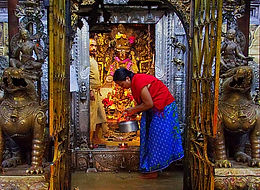 Nepalese woman caretaking the shrine at Golden Temple, Patan, Nepal