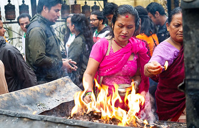 Two nepali women lighting offerings from fire in crowd at Swaymbhunath Temple