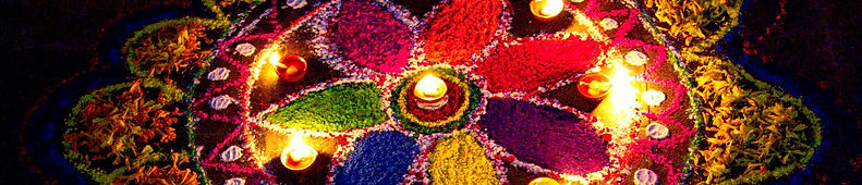 A mandal on the sidewalk, made with colourd powders and flowers, lit by candles.  Kathmandu, Nepal