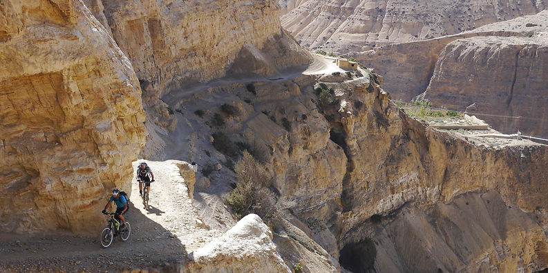 Mountain bike riders on winding mountain track during Yak Attack race in Mustang, Nepal