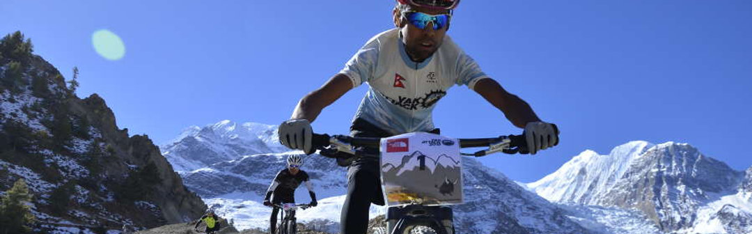 Mountain bike riders in snow on Yak Attack race, Annapurnas, Nepal