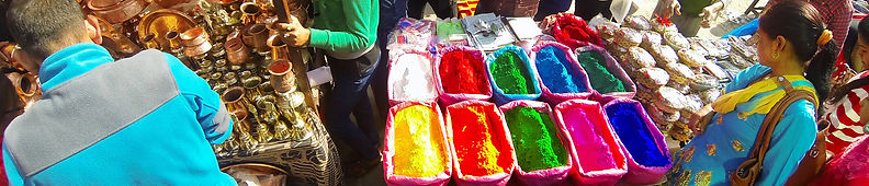 Nepali woman looking at coloured powders and copper kitchen products in Asan Tole, Kathmandu