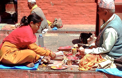 Nepali mand and woman perfoming offerings in the street, Patan, Nepal