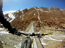 Mountain bike rider about to cross suspension bridge in UpperMustang, Nepal