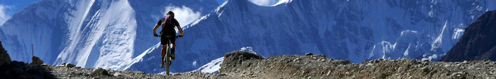 Mountain bike rider on trail in front of snowy mountains, Nepal