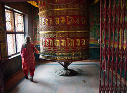 Old nepali woman spinning giant prayer wheel atGuru Lhakhang Monastery, Boudhanath Stupa, Nepal