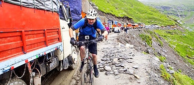 Cyclist riding past trucks, dirt rad, Annapurna, Nepal