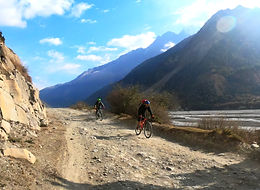 Two mountain bike riders on trail next to river in Mustang, Nepal