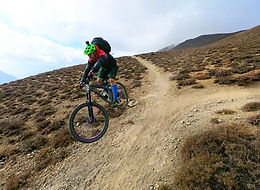 Mountain bike rider descending trail in Uppe Mustang, Nepal