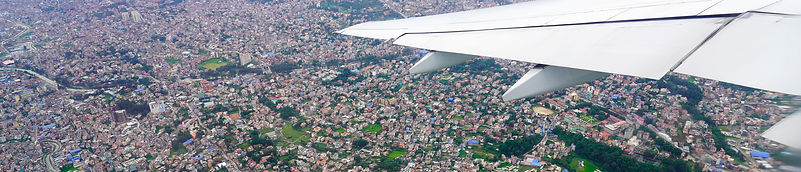 View from plane window showing plane wing and Kathmandu below