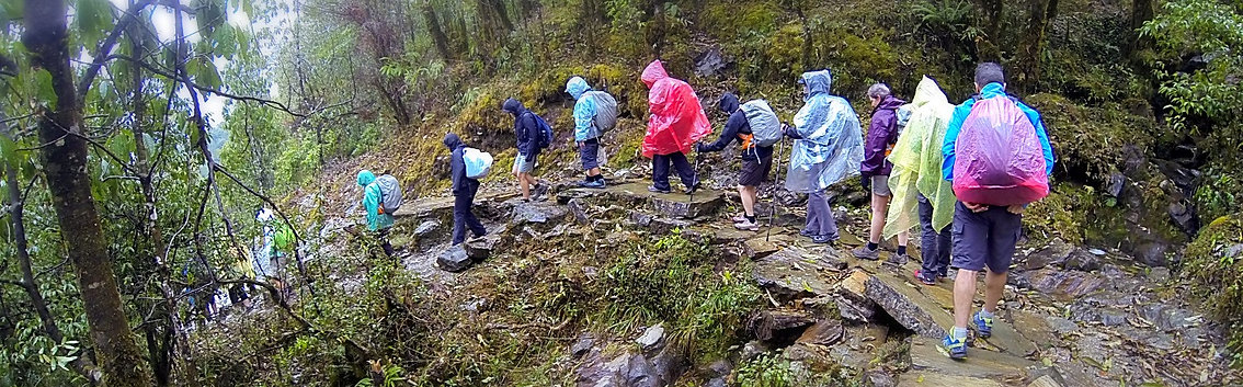 Wanderlust Journeys group walking down steep trail in the rain, in Nepal