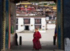 Monk walking through th massive entrance doors at Tashilhunpo Monastery, Shigatse, Tibet