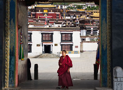 Monk walking through th massive entrance doors at Tashilhunpo Monastery, Shigatse, Tibet