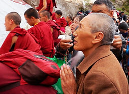 Nun praying in front of the giant Thangka for Shoton at Drepung Monastery near Lhasa, Tibet