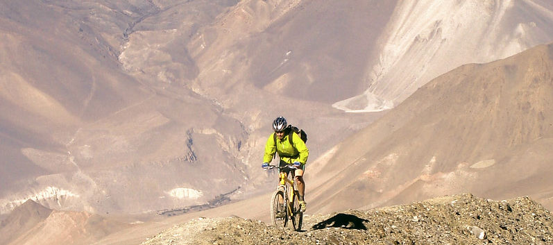 mountain bike rider climbing up mountain in Upper Mustang, Nepal