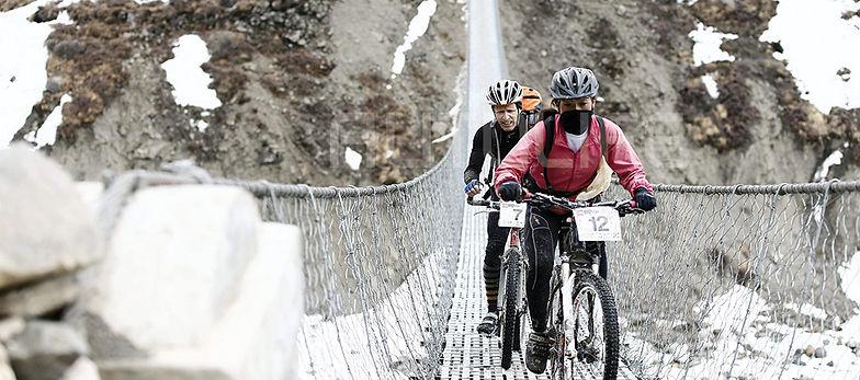 Mountain bike riders crossing steel cable bridge during Yak Attack race, Nepal