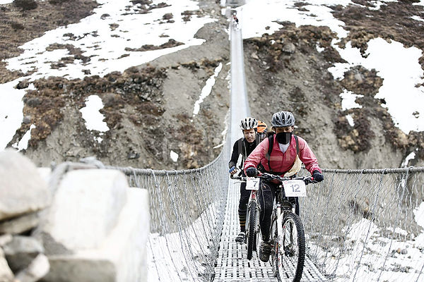 Mountain bike riders crossing steel cable bridge during Yak Attack race, Nepal