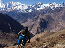 Mountain bike rider hading down valey in Upper Mustang, Nepal