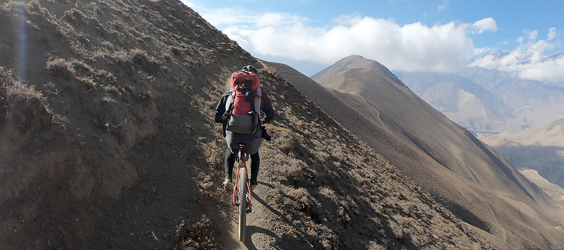 Mountain Bike rider climbing up mountain side in Nepal