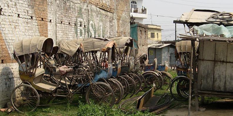 Rickshaw wrecks lined up in frnt of brick wall, Kathmandu, Nepal