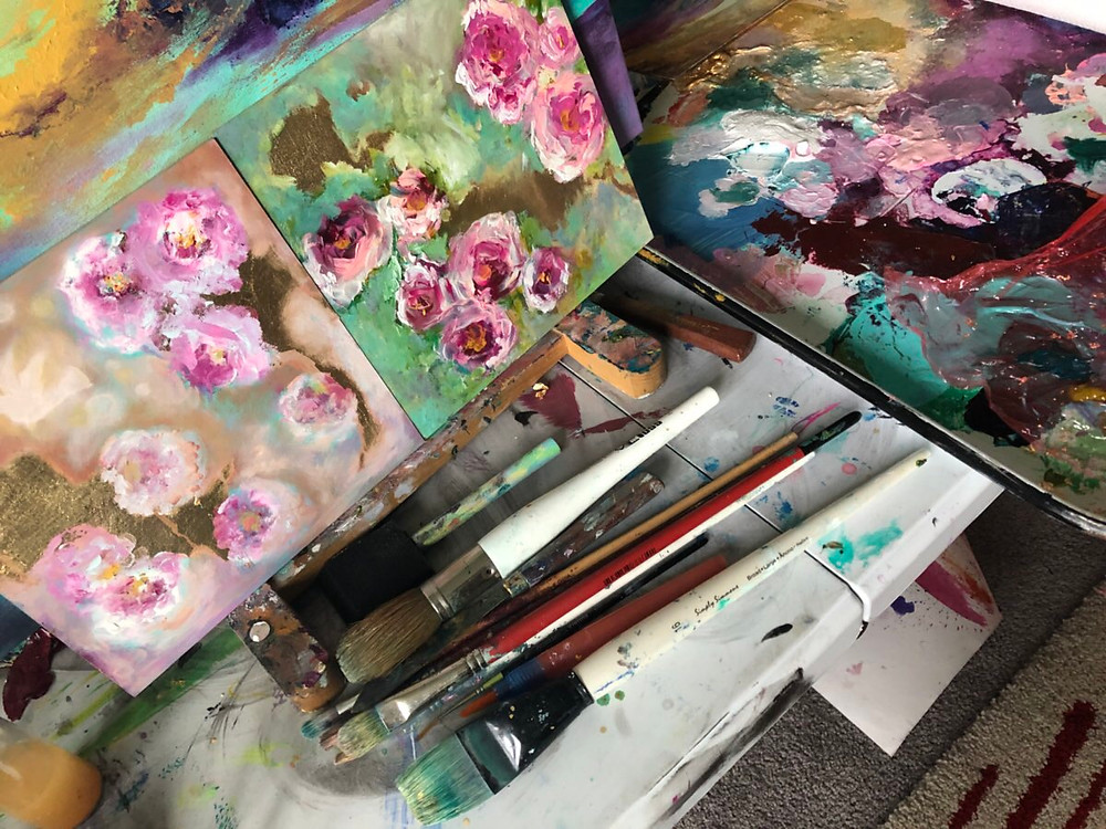 Two artist canvases with pink roses and a paint pallette