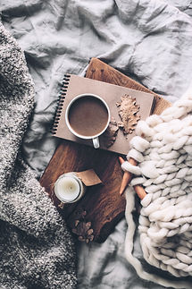Cup of coffee and candle on rustic wooden serving tray in the cozy bed with blanket. Knitt