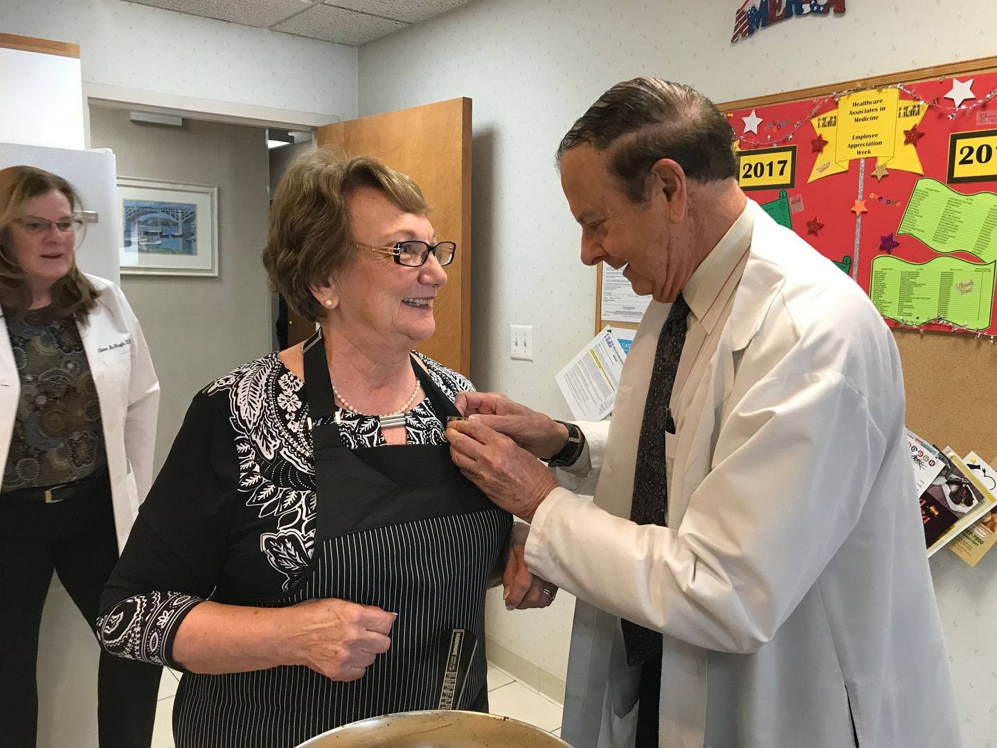 Neurologist, Dr. Kulick pins Kathy T. for years of service