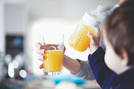 orange juice in a glass and a baby bottle
