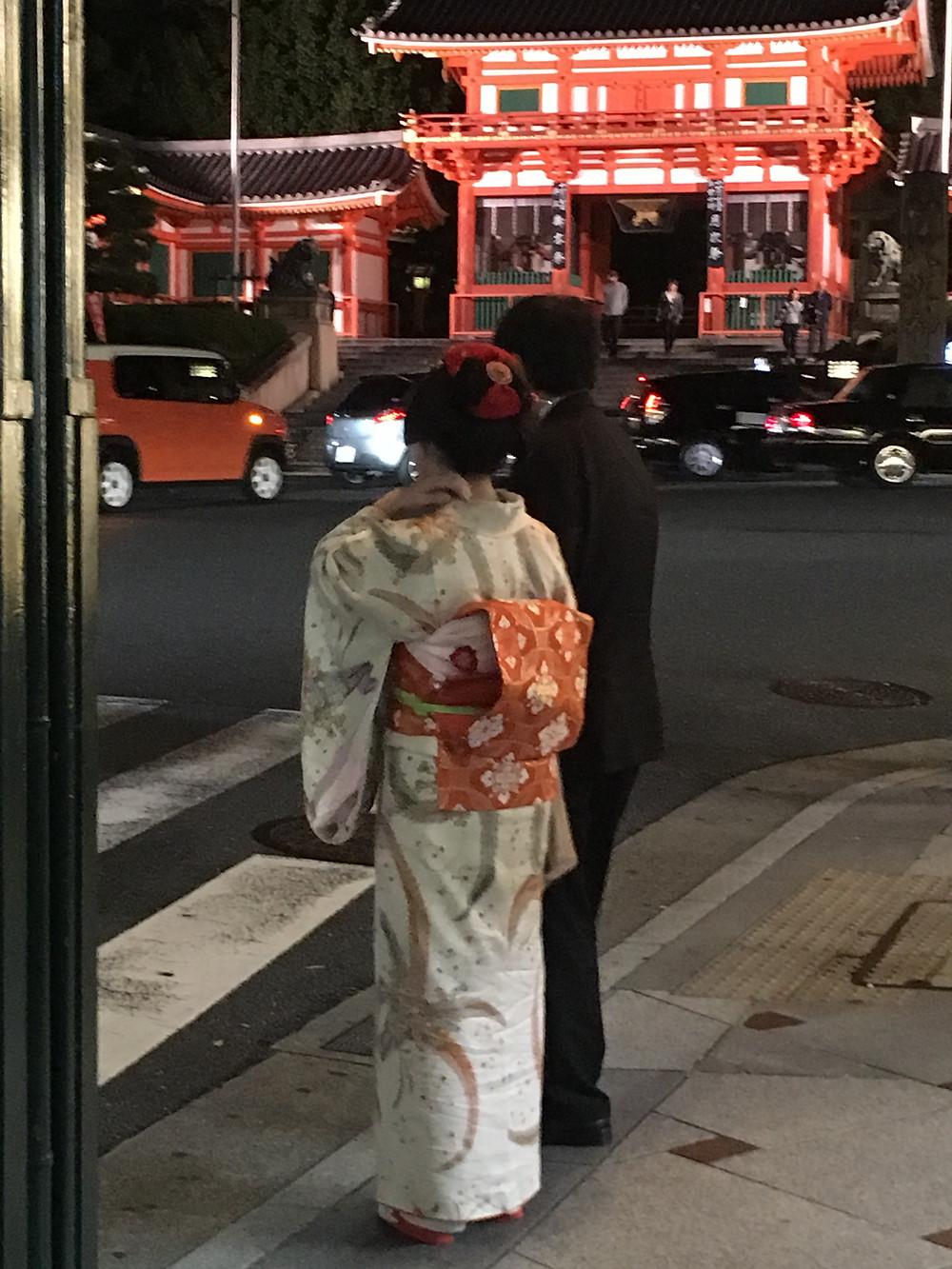 gueixa parada no sinal, do lado de um homem, ao fundo o Santuáro Yasaka-jinja,