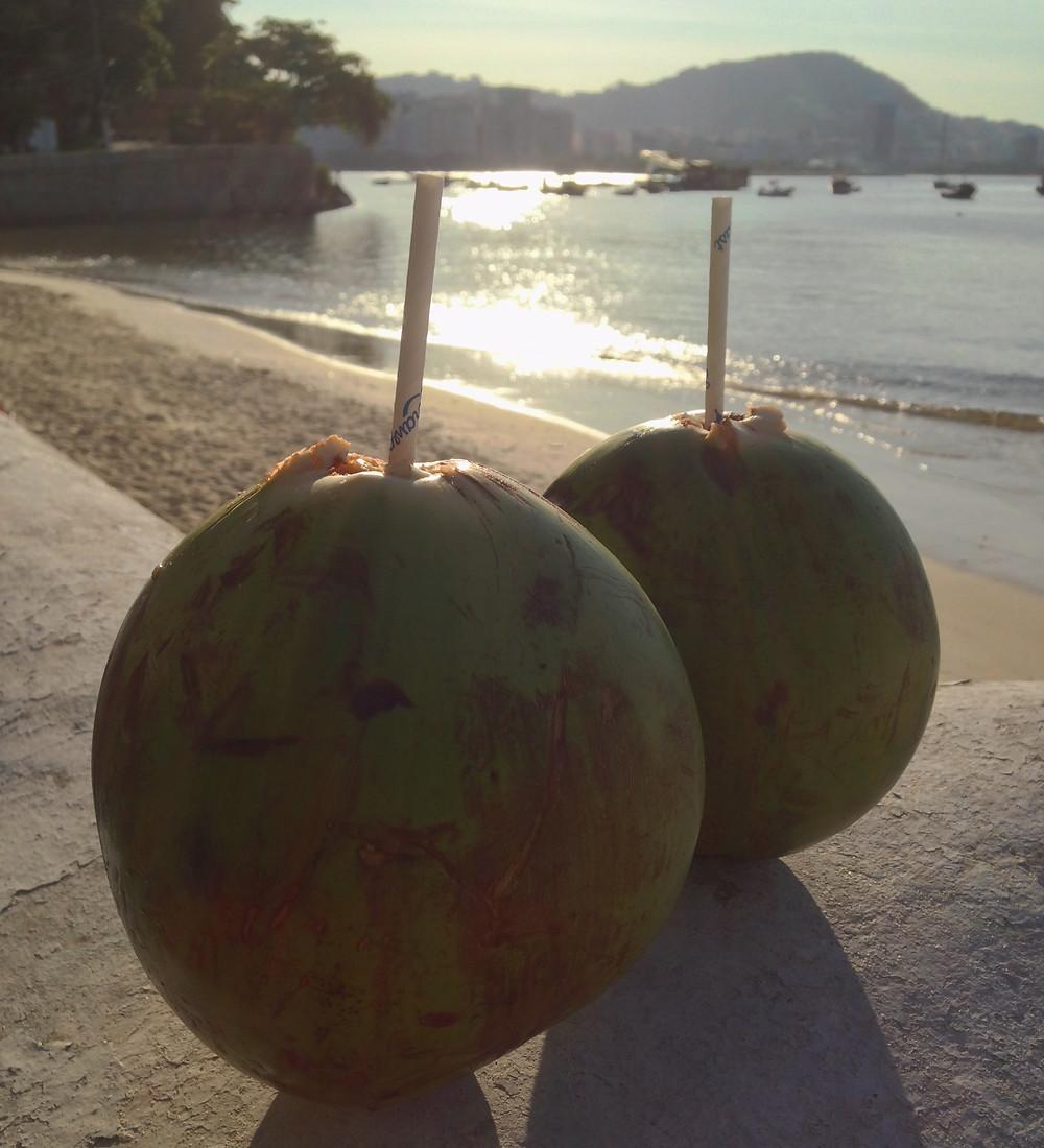 Por do sol com praia e água de coco