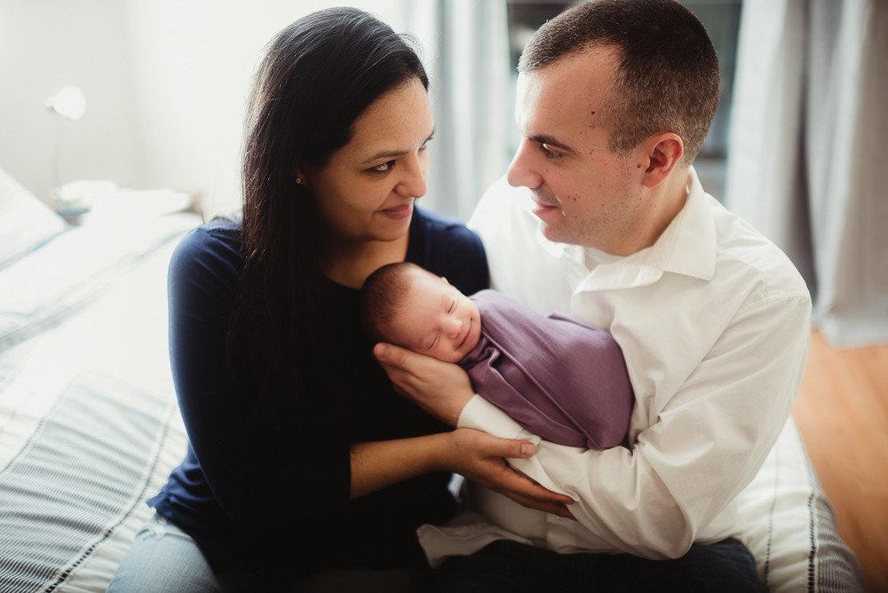 newborn girl with parents smiling