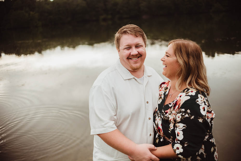 husband and wife embrace waterfront