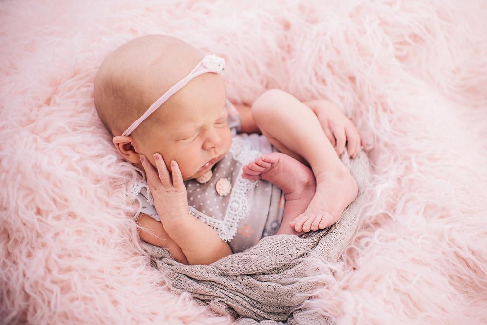 newborn girl hands on face