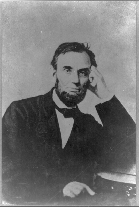 Abraham Lincoln, seated, with his left hand on his face, 1863