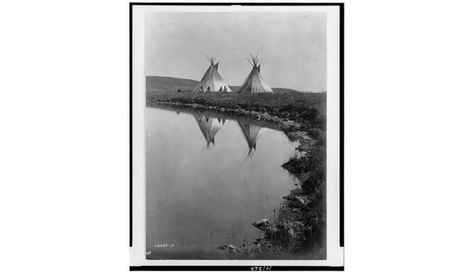 two tepees reflected in water of pond, with four Piegan Indians seated in front of one tepee, Montana, c1910