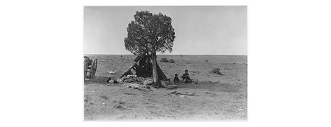 Temporary Indian camp. Note, Indian woman spinning wool. Also balls of yarn prepared for blanket weaving in foreground. Southern Navajo Agency, 1933