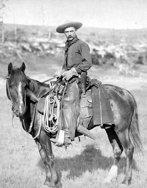 A man on a horse dressed in cowboy attire in Sturges, Dakota Territory. Photograph taken in 1887