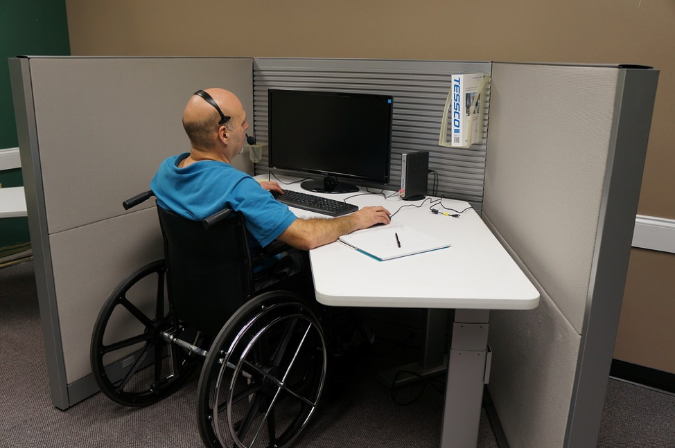 Man in wheelchair working at a computer workstation