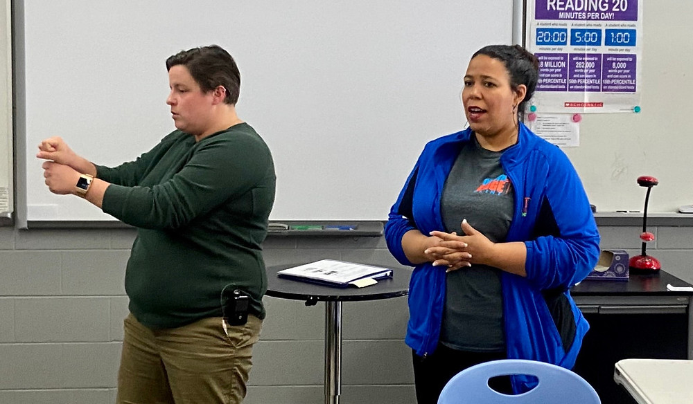 Two people standing at the front of a classroom, one is signing the other is speaking