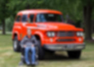 Smilingman outdoors in a wheelchair in from of an orange 1958 Dodge Power Wagon