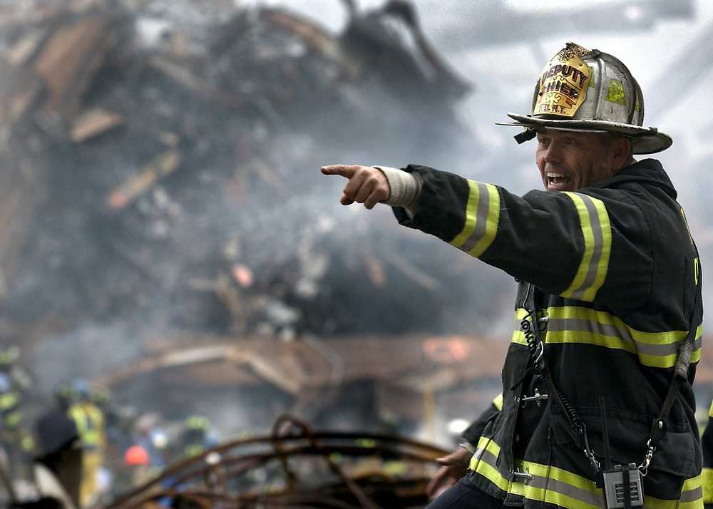 Firefighter pointing while standing in front of a collapsed structure