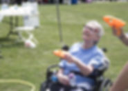 Smiling woman with gray hair in wheelchair holding a squirt gun