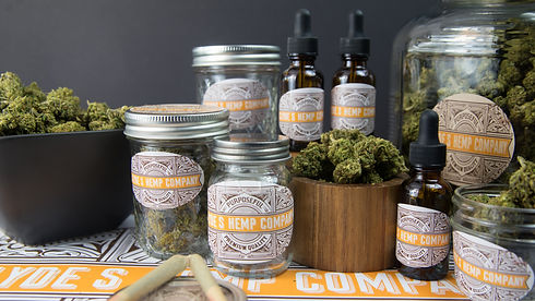 Clydes hemp company CBD products displayed on a table with clydes hemp company logo with CBD oil and CBD tinctures in the background. The CBD hemp flower are displayed in glass mason jars