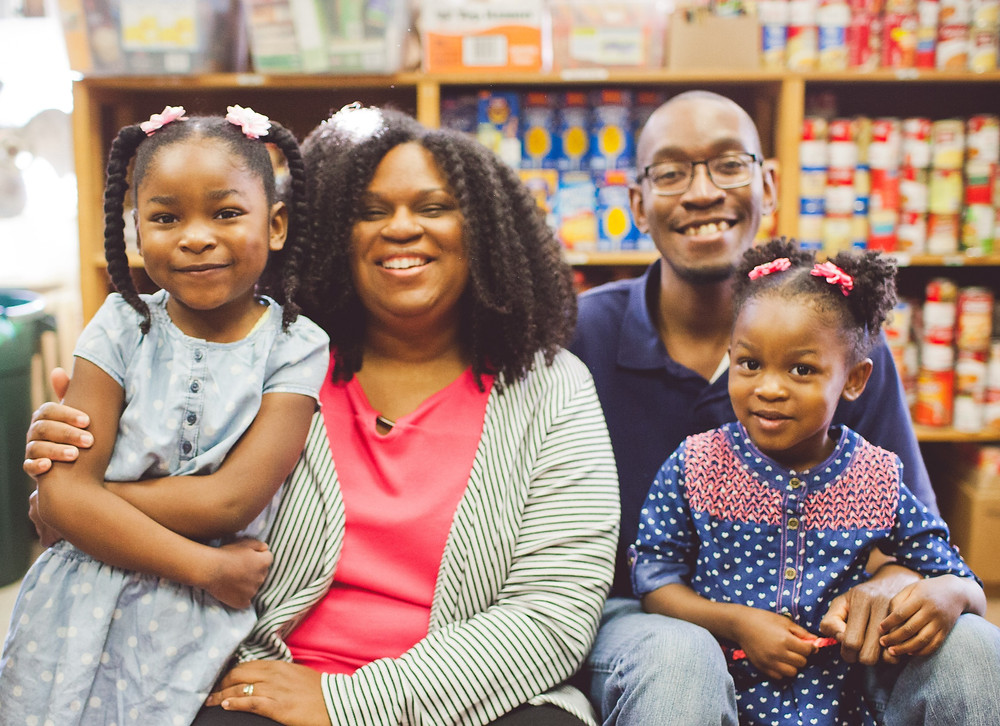 family-of-four-with-two-children-sitting-in-food-pantry