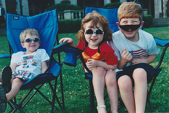 three-little-kids-in-blue-chairs-with-sunglasses-smiles