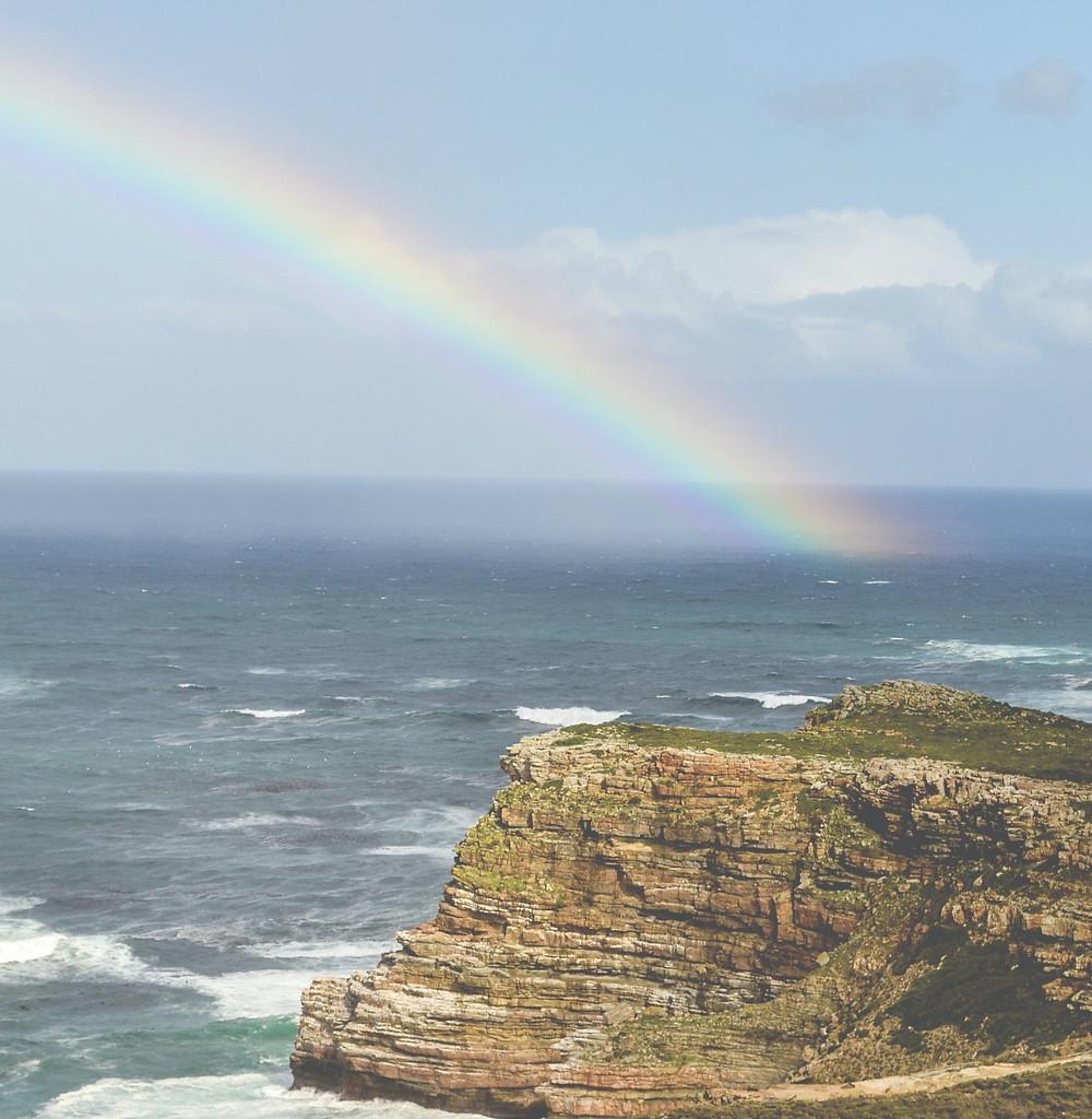 rainbow-over-ocean-bordered-by-cliff